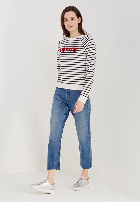 Девушка в синих джинсах с необработанным краем, полосатом свитшоте и кроссовках