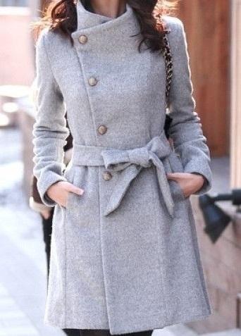 Девушка в стильном, сером пальто с бантиком спереди