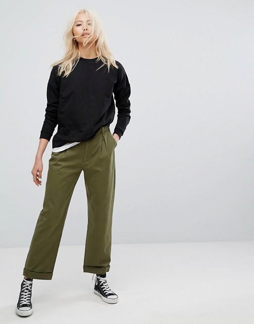 Девушка в укороченных брюках, джемпере и кедах