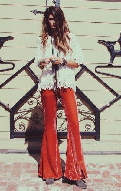 Девушка в ярких штанах клешь, браслетами на руках и украшениями на шее