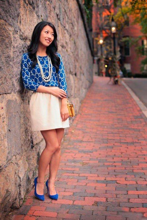 Девушка в юбке колокол в синих туфлях и блузе с бусами в цвет юбки