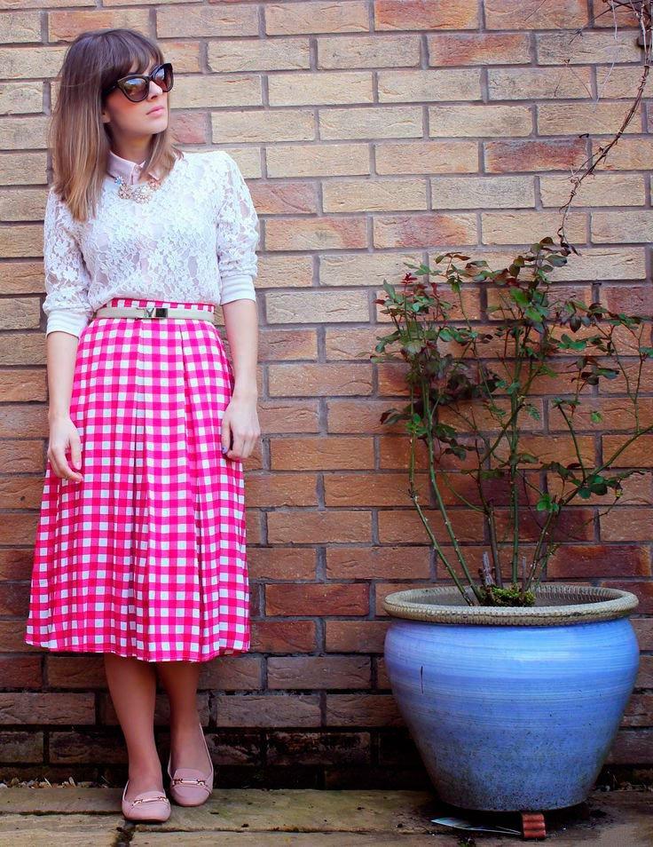 Девушка в юбке миди с розовым принтом в клетку