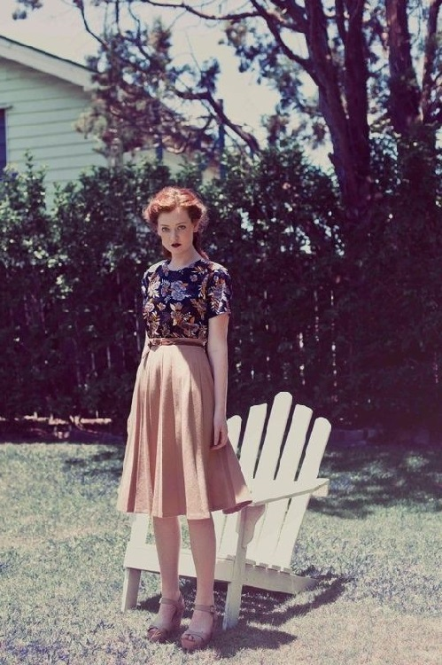 Девушка в юбке, ниже колен, и блузе в цветочек, лук в стиле 70-х