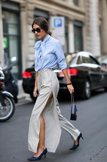 Девушка в юбке с высоким разрезом и блузе с бантиком
