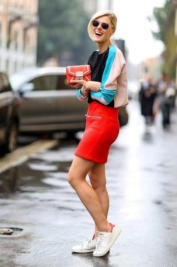 Девушка в юбтягивающей, кожаной юбке, кроссовках и спортивной кофте