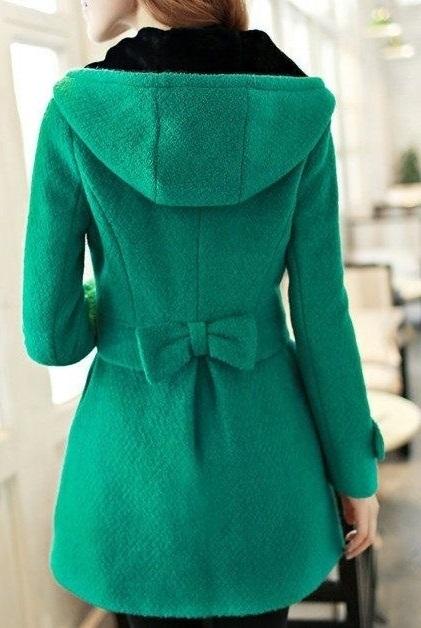 Девушка в зеленом пальто с капюшоном и бантом сзади