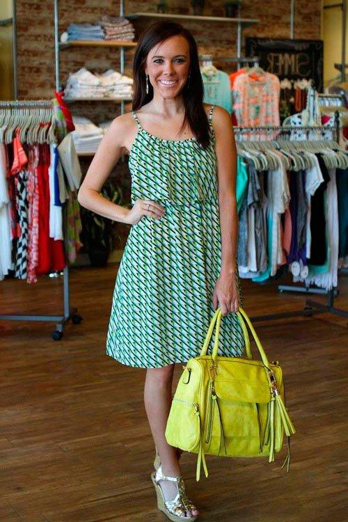 Девушка в зеленом платье с принтом, яркой зеленой сумкой и золотистыми босоножками