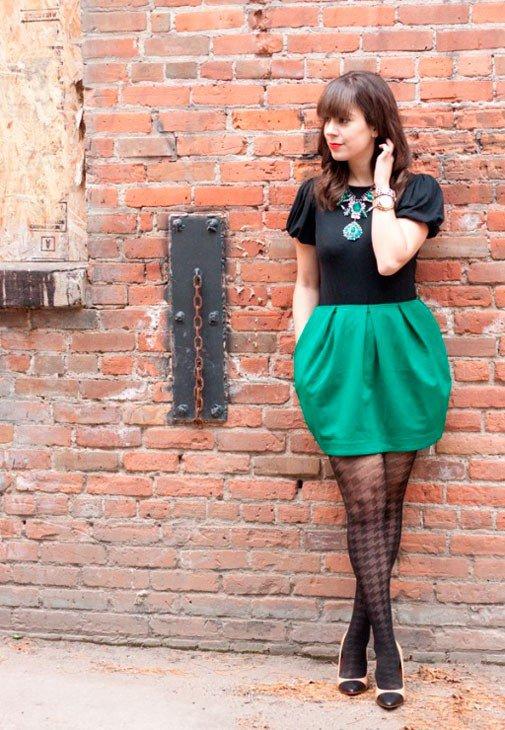 Девушка в зеленой юбке колокол и черном топе с крупным украшением на шее