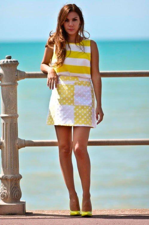 Девушка в желто белой юбке и топе, и в желтых туфлях