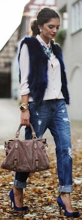 Девушках в джинсах бойфрендах, белой блузе и меховом жилете