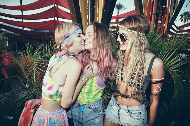 Девушки хиппи в джинсовых шортах и цветных топах