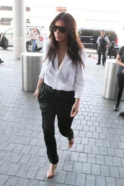 Ким Кардашян в черных штанах, белой блузе и туфлях лодочках