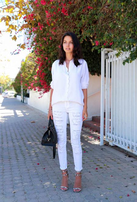 Модель в белых джинсах и блузке, черная сумка и босоножки