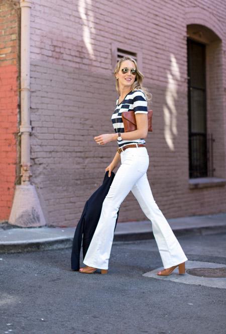 Модель в белых джинсах клеш и черно-белой футболке