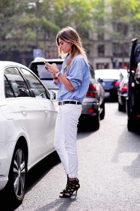 Модель в белых джинсах с черным ремнем, рубашка и черные босоножки