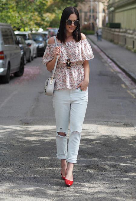 Модель в белых джинсах, топ с цветочным принтом, маленькая сумочка
