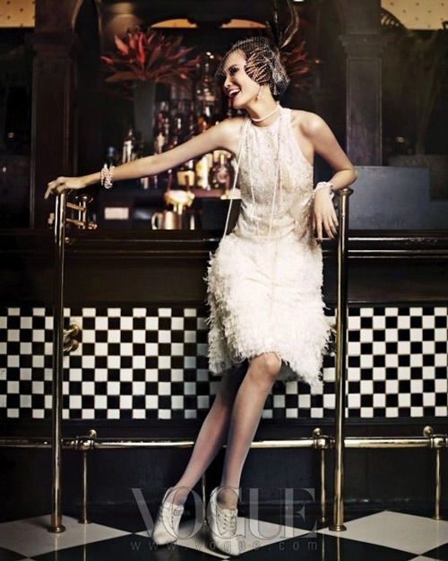 Модель в бежевом платье без рукавов в стиле Гэтсби и шляпкой с перьями