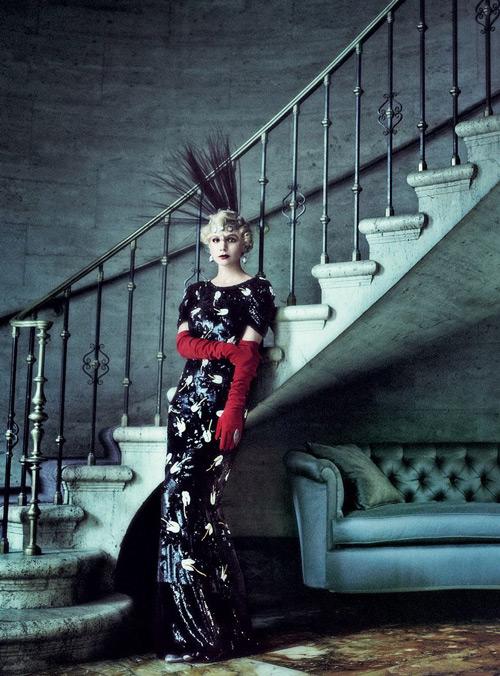 Модель в черном блестящем платье макси, высоких красных перчатках и шляпка с перьями