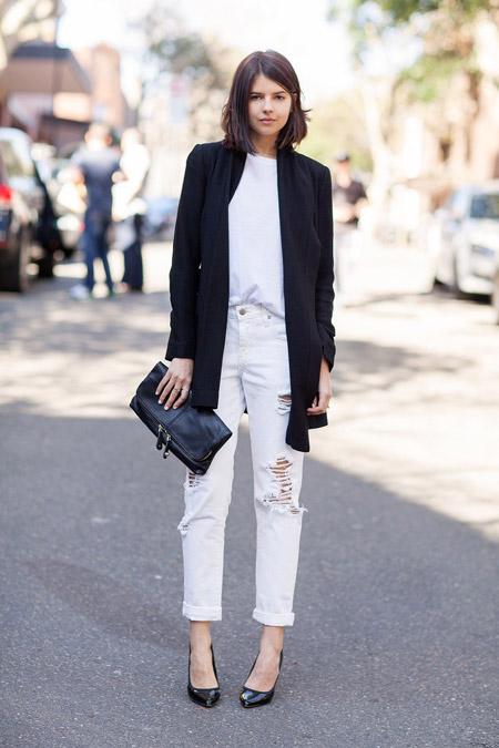 Модель в джинсах прямого кроя, черный кардиган, клатч и туфли лодочки