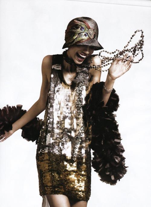 Модель в коротком блестящем платье с паетками, шляпкой с перьями павлина в стиле Гэтсби