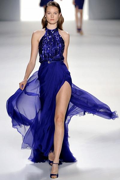 Модель в нарядном платье с пайетками, летящим подолом и глубоким разрезом