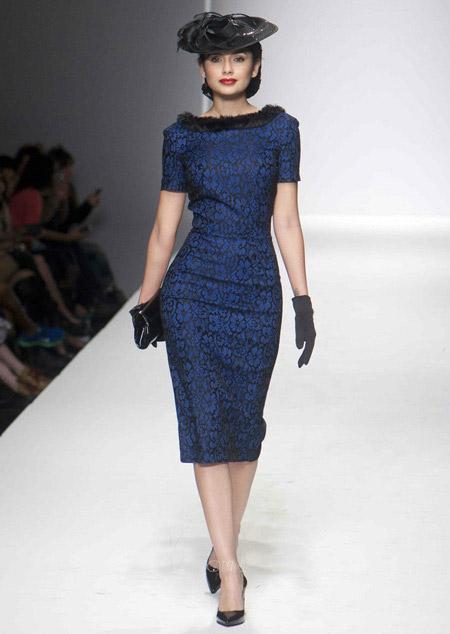 Модель в сине черном платье-футляр с меховым воротничком