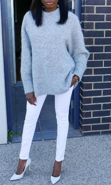 Модель в узких белых джинсах, туфли лодчки и объемный серый свитер