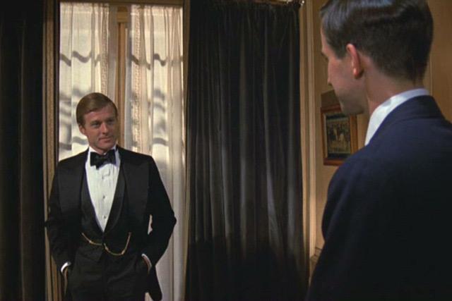 Молодой человек в элегантном черном костюме тройка с белой рубашкой и бабочкой в стиле Гэтсби
