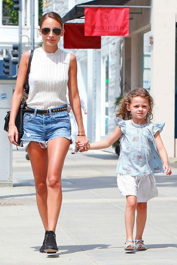 Николь Ричи в коротких джинсовых шортах белом топе идет по улице с дочкой за руку