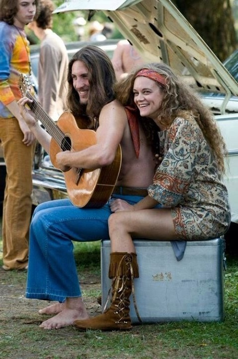 Парень хиппи в джинсах клешь играет на гитаре