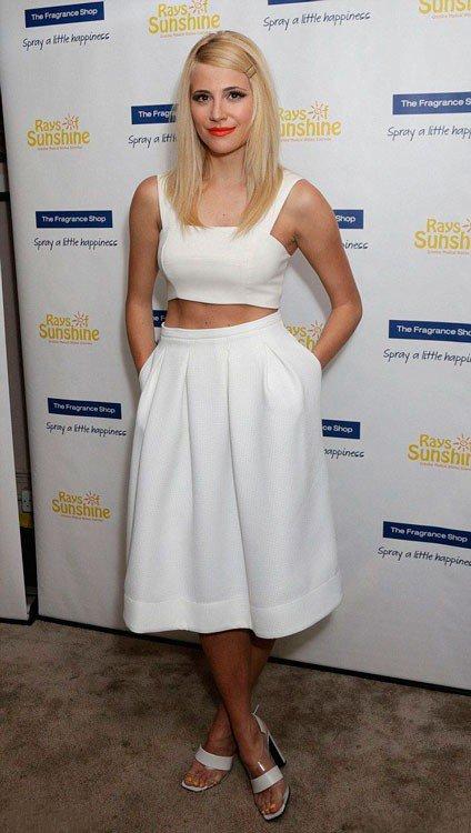 Пикси Лотт в белой, широкой юбке миди и белом коротком топе
