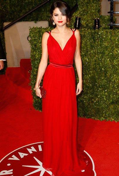 Селена Гомес в вечернем, красном платье, дополняют образ крупные, золотые серьги и золотой браслет