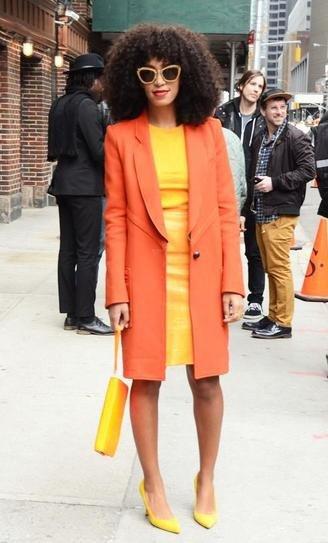 Соланж в оранжевом пальто и желтом платье