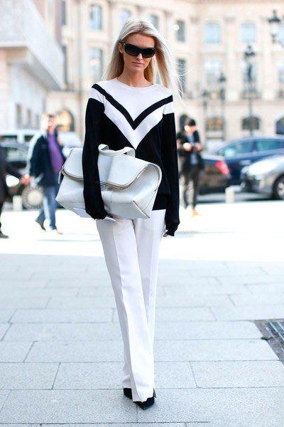 Девушка в белых брюках и черно-белом свитере