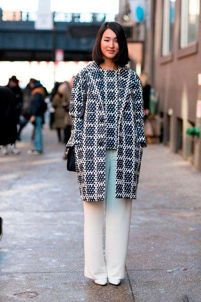 Девушка в белых штанах и пальто с ярким принтом