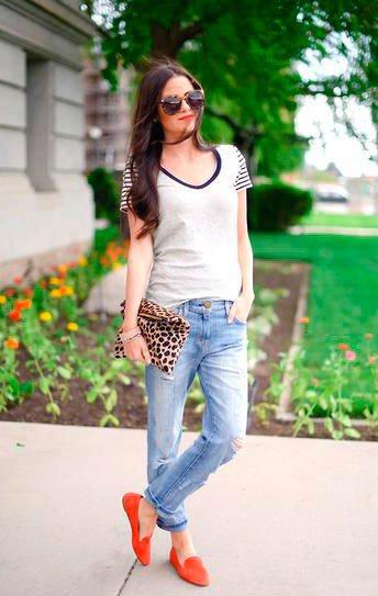 Девушка в джинсах и красных туфлях, а в руках клатч с принтом