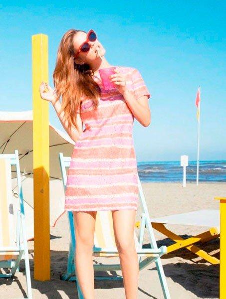 Девушка на пляже в цветном платье, пьет коктейль