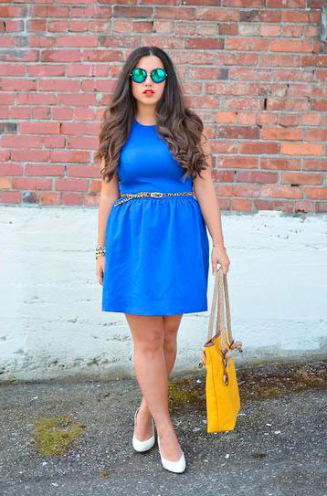 Девушка в синем платье с элегантным ремнем и желтой сумкой