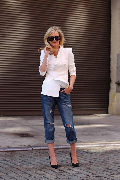 Девушка в рваных, подвернутых бойфрендах и белом пиджаке