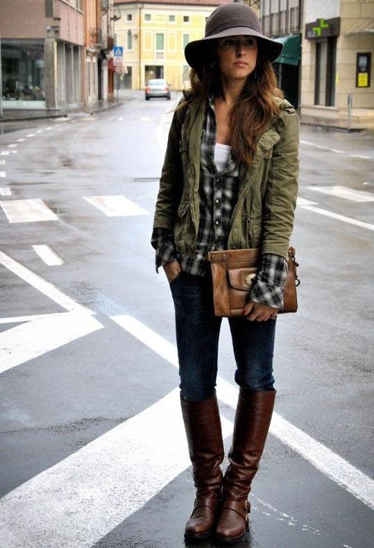Девушка в куртке цвета хаки, джинсах и сапогах до колена в стиле милитари