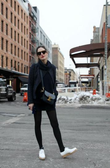 Девушка в белых кроссовках и коротком, черном пальто