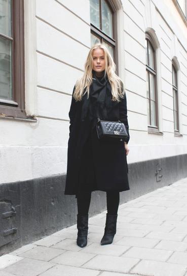 Девушка в черном пальто и коротких сапогах