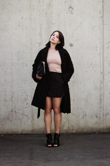 Девушка в черной юбке, топе, ботильонах и пальто