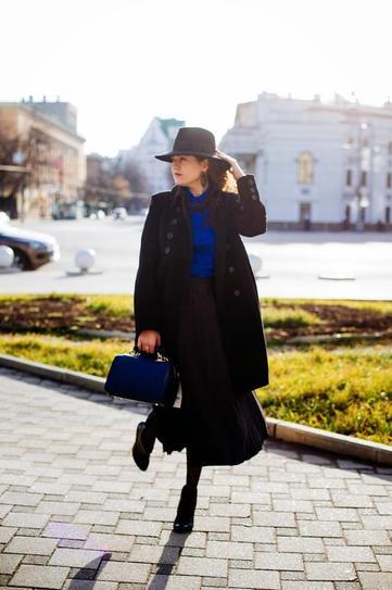 Девушка в длинной юбке, шляпе и черном пальто