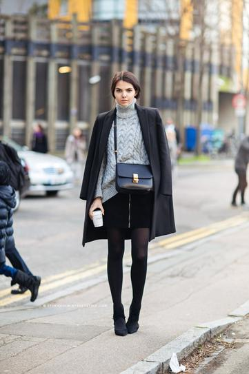 Девушка в короткой, черной юбке, свитере и пальто