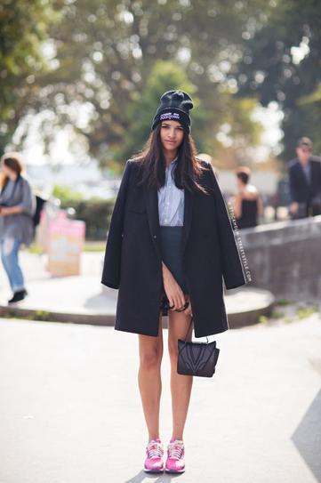 Девушка в короткой юбке, кроссовках и черном пальто