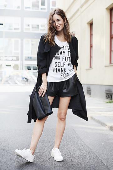 Девушка в кожаных шортах, кроссовках, футболке и пальто
