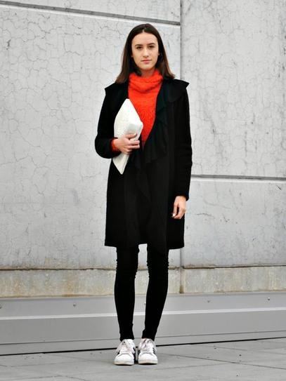 Девушка в обтягивающих джинсах, кроссовках и пальто