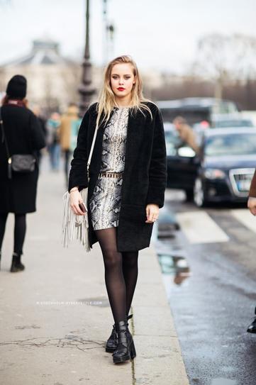 Девушка в платье, черном пальто и с сумкой с бахромой