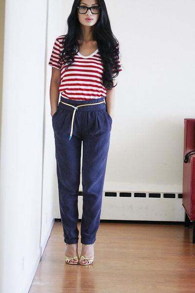 Девушка в полосатой футболке, темно-синих штанах и на каблуках